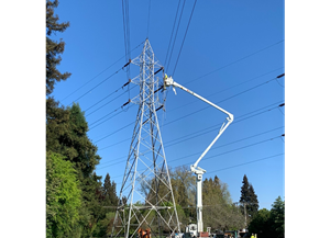 Transmission line upgrade in progress with line worker at tower