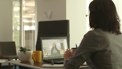 Woman sitting at a desk looking at a virtual meeting on her laptop computer