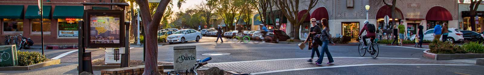 Panoramic photo of the City of Davis with women crossing the street and a biker riding.