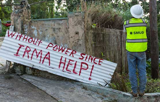 SMUD worker in front of a sign that says, 'Without power since Irma help!'