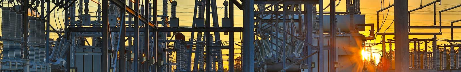 Sunset at a substation with electrical equipment in the foreground.