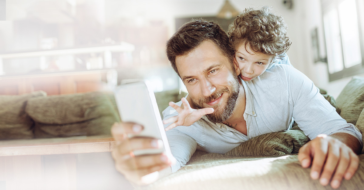 Dad holding a phone on the couch with his son on his back reaching for the phone.