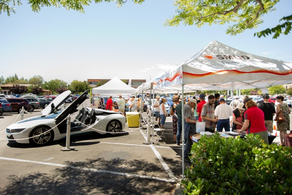 SMUD ride and drive event with people getting information at tables and an electric vehicle displayed on site.