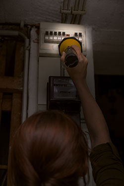 woman with flashlight at breaker box