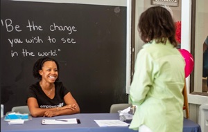 "Woman behind a desk with a woman in front. ""Be the change you want to see in the world"" is written on a black board."