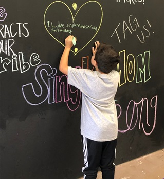 Young student writing on chalk board