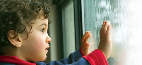 Boy looking out window at rain