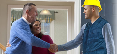 Service person shaking hands with homeowners