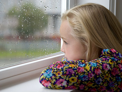 girl watching rain through window