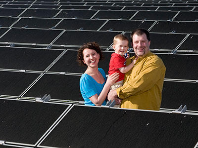 family in front of solar panels