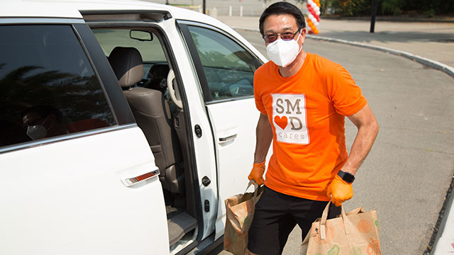 CEO Paul Lau loading groceries into a car wearing a SMUD Cares t-shirt